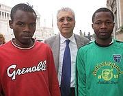 L'assessore Lo Fazio con due immigrati di Rosarno (Fotogramma)